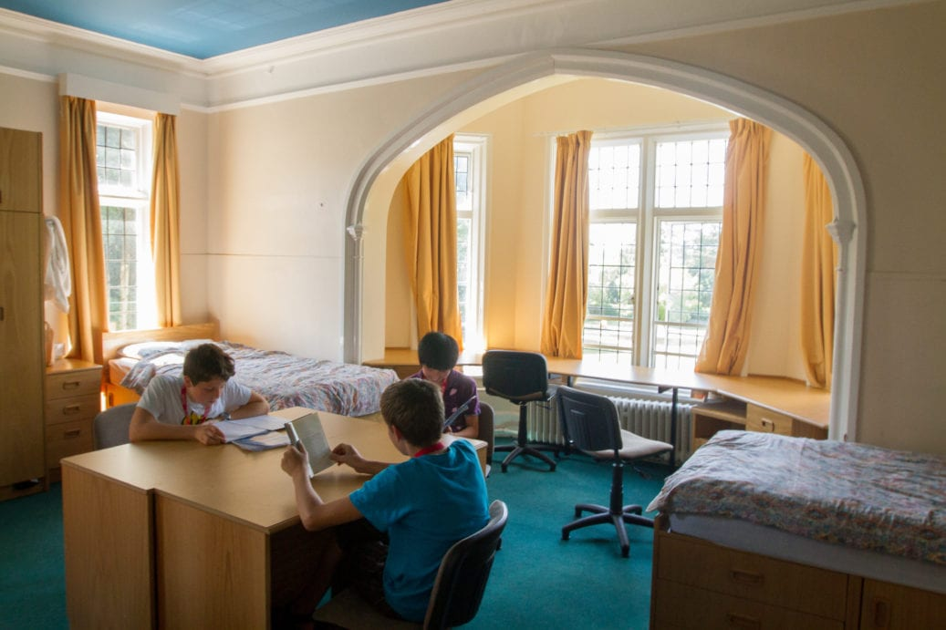 Three students studying in multi-bed room with multiple desks at Sir Henry residential English summer camp