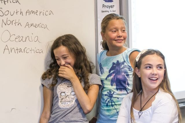 Three students laugh by the whiteboard in English language class at Sir Henry residential English summer camp. Visible writing on the board reads: 'South America, North America, Oceania, Antarctica'.
