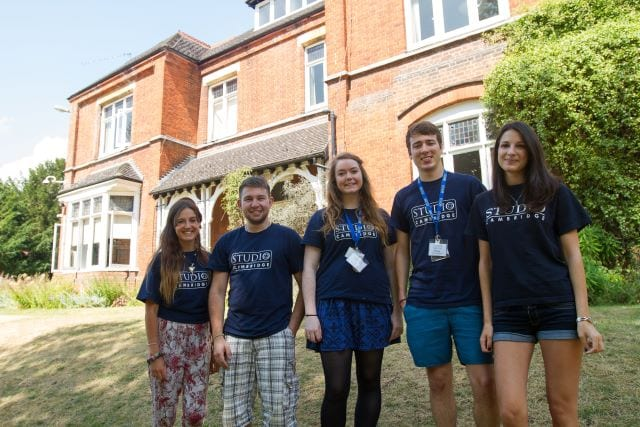 Welfare team at Sir Laurence residential English summer camp smile on lawns of Lucy Cavendish college