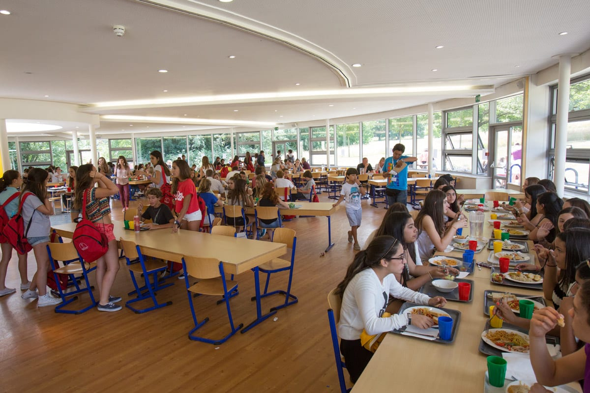Students eat lunch in dining hall at Sir Richard residential English summer camp, based in Leighton Park School