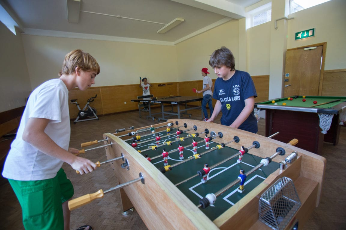 Students play table football (foosball) and table tennis in games room at Sir Richard residential English summer camp