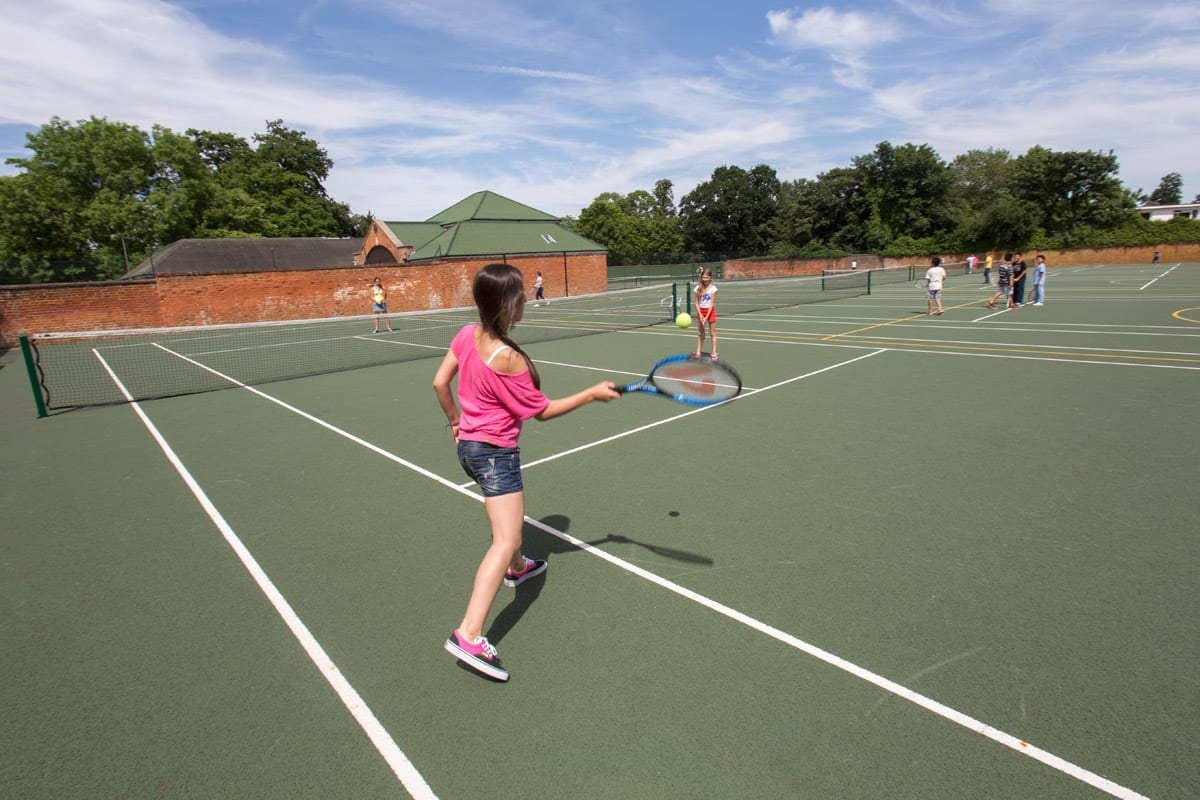 Students playing tennis on tennis courts at Sir Richard residential English summer camp