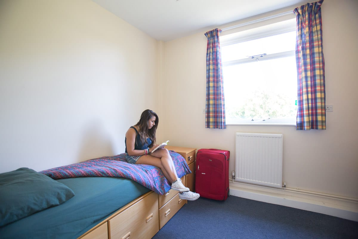 Student reads on single bed with built-in storage space at Sir Richard residential English summer camp, based in Leighton Park School