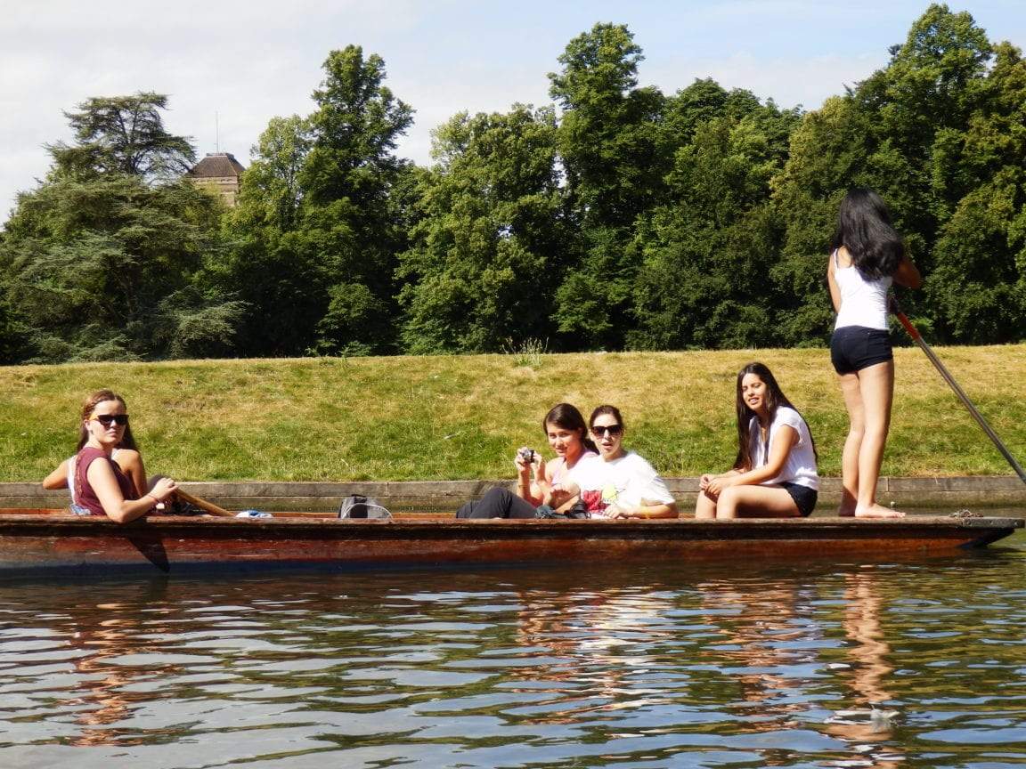 A group of Sir Christopher English summer camp students punting on the River Cam on a sunny day