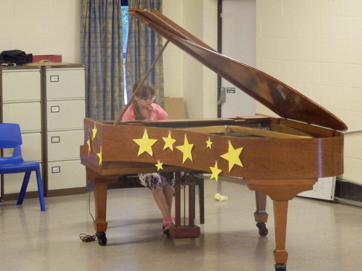 Student plays grand piano in King's Ely at Sir Edward residential English summer camp