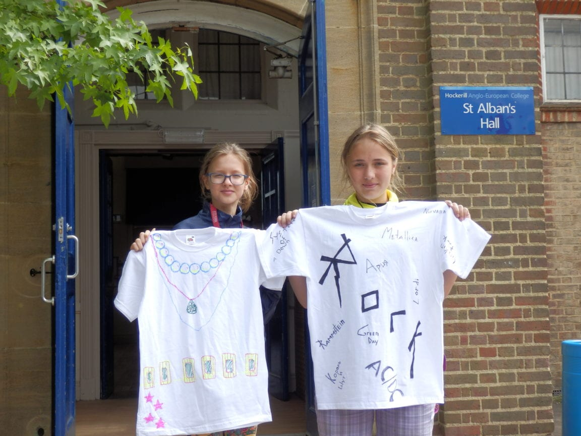 Two students hold up t-shirts they designed in creative activity at Sir Henry residential English summer camp