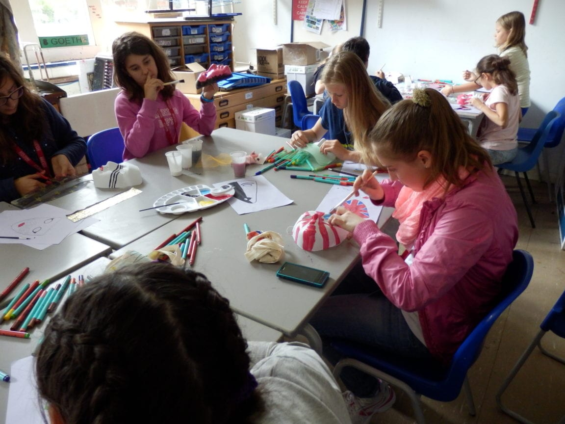 Group of students paint masks in creative activity at Sir Henry residential English summer camp
