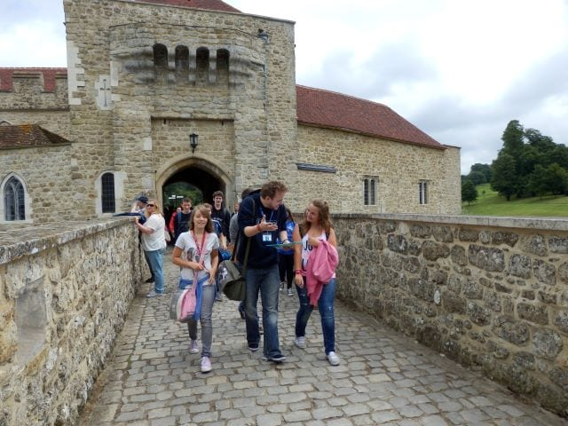Teacher answers student questions on excursion to English historical castle at Sir Henry residential English summer camp