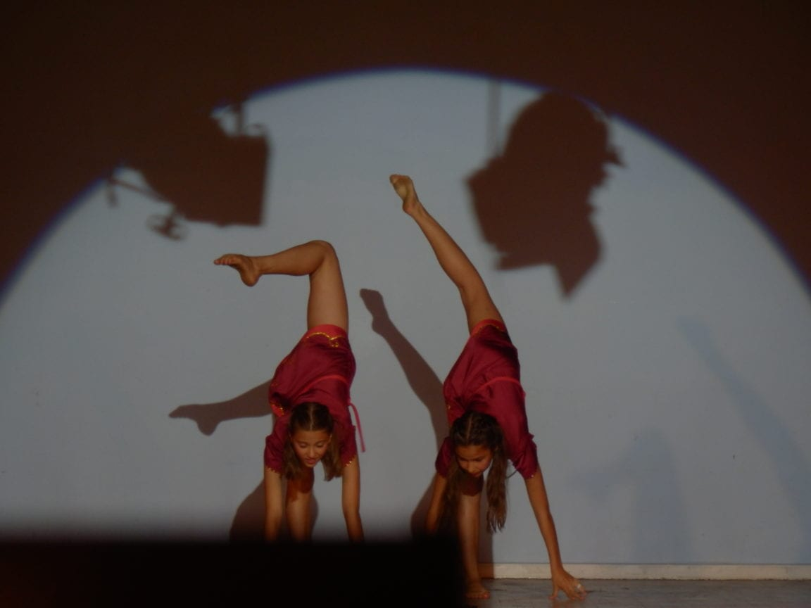 Two students doing a dance routine in spotlight on stage at Sir Henry residential English summer camp
