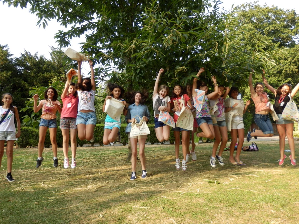 Students at Sir Henry residential English summer camp laugh and jump in a line with personally customised tote bags