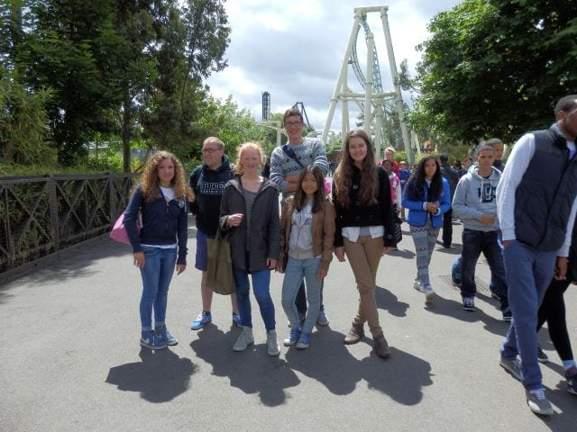 Students pose for photograph at Thorpe Park with rides visible in background, on excursion at Sir Michael English summer camp