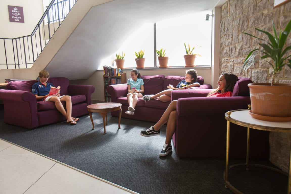 Four students relax on sofas in common area at Sir Richard residential English summer camp