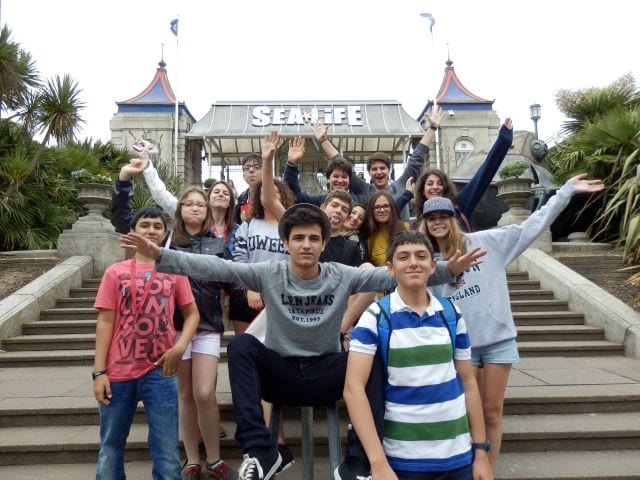 Group of students from Sir William residential English summer camp pose on steps at Sea Life entrance