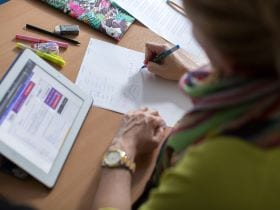 An image of a student working hard in an English lesson at Studio Cambridge, linking to a page on Exam Courses where you can find out more about learning English in Cambridge