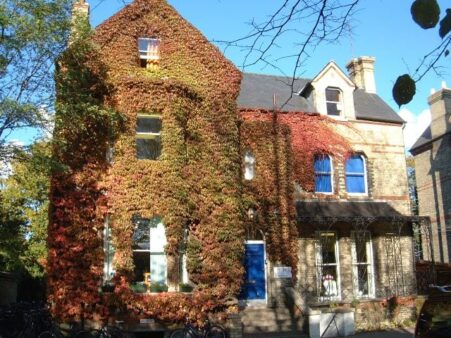 Studio Cambridge Main School in Autumn. There is a Virginia Creeper with red and yellow leaves climbing the school exterior