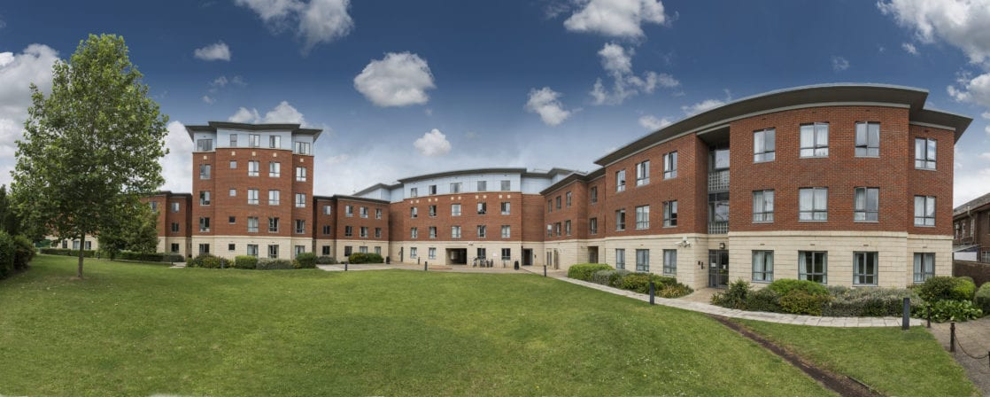 A pano photo of Tripos Court our residential accommodation for adults at Studio Cambridge. A modern building with a large lawn.