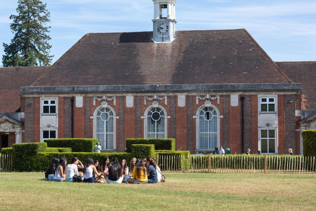 Students on lawn outside accommodation block at Sir Richard residential English summer camp