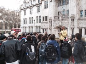 An image of a large group of students facing a tour guide in London on an excursions at an English language school, linking to a page on a year-round camp for teenagers and young adults