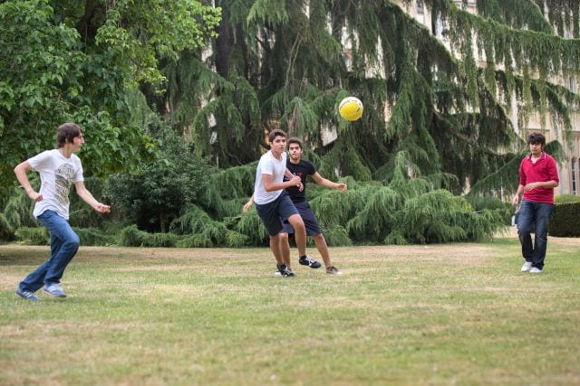 Sir William residential English summer camp students playing football on lawns at Richmond the American International University