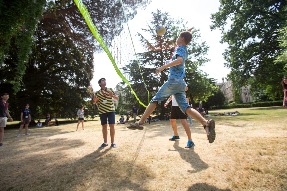 Students play volleyball on lawns at front of Richmond the American International University