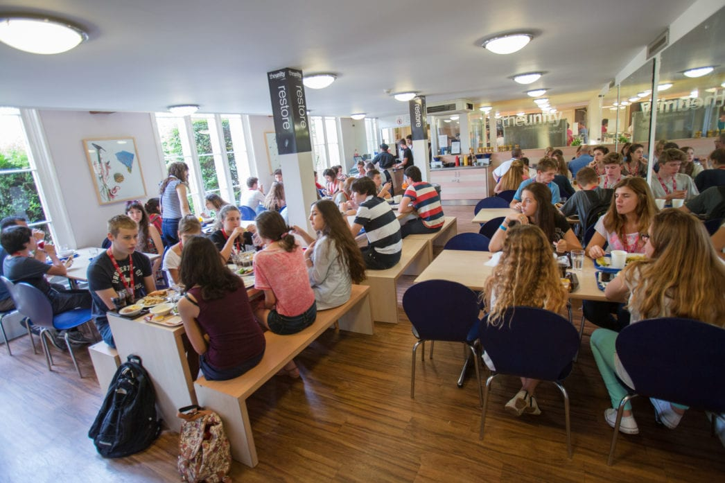 English students at Sir William summer camp eat lunch in the refectory or dining hall of Richmond the American International University in London