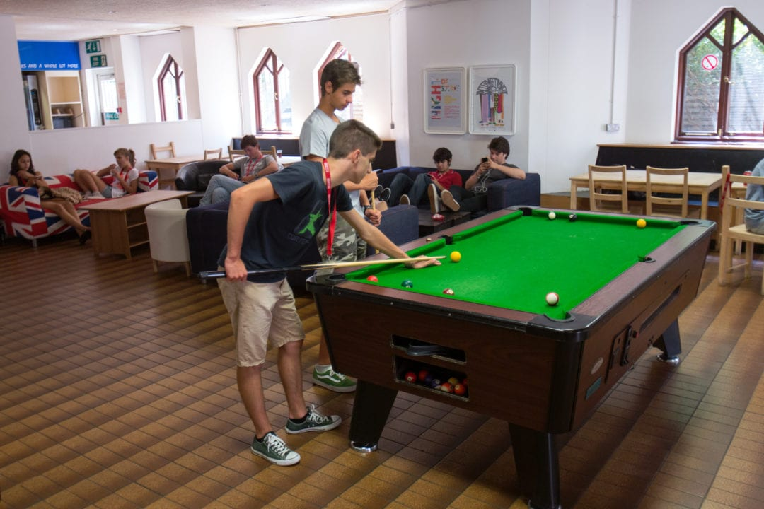 Students playing pool in student common area at Sir William English summer camp