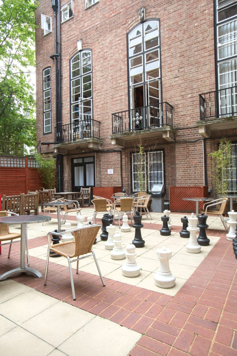 Courtyard with tables and giant chess pieces at Richmond the American International University in London, base for Studio Cambridge English summer camp