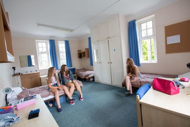 Three girls sit in multi-bed room with large wardrobe and several desks at Sir William residential English summer camp