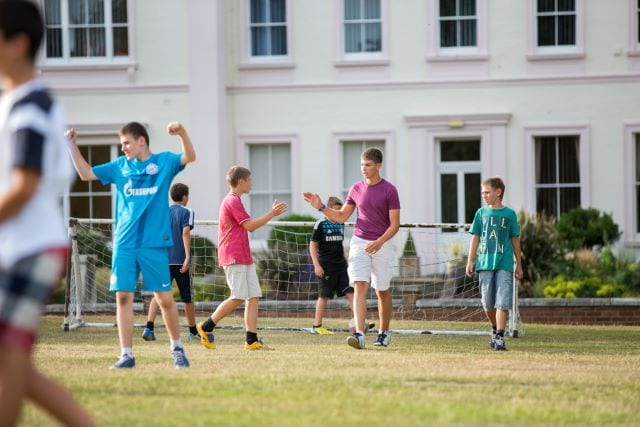 Students congratulate each other on football pitch after a match at Sir RIchard residential English summer camp