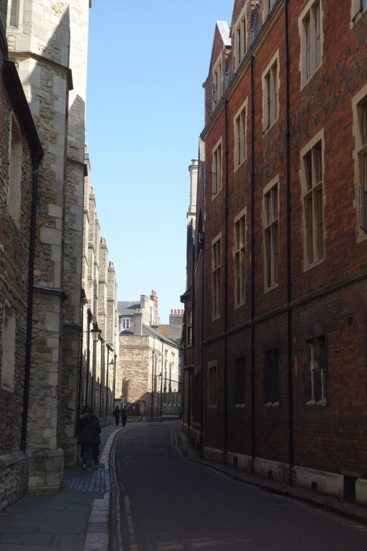 A narrow street in the city of Cambridge, UK, with redbrick buildings on the right and old stone buildings on the left.