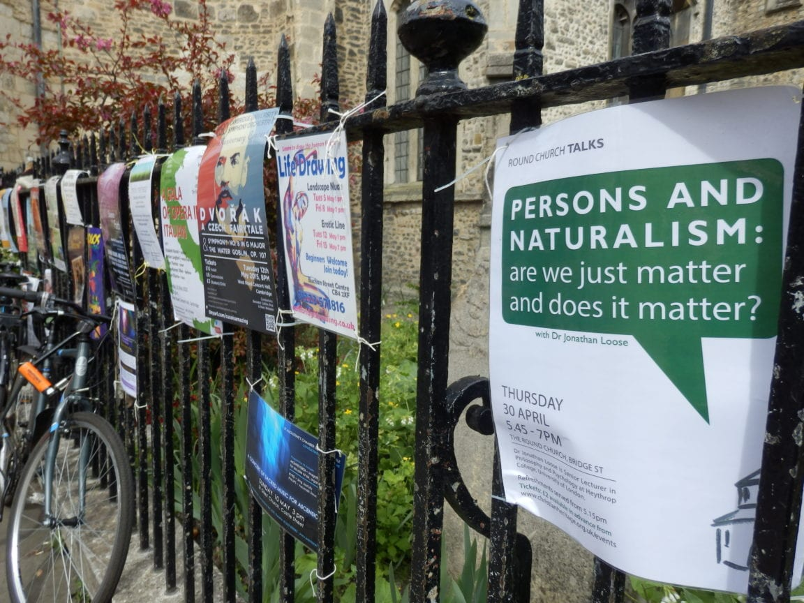 Academic talk posters on railings outside Round Church, Cambridge.