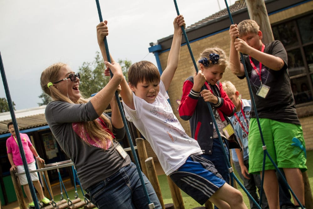 Group of young children from Sir Edward English language summer camp playing on a playground at King's Ely.