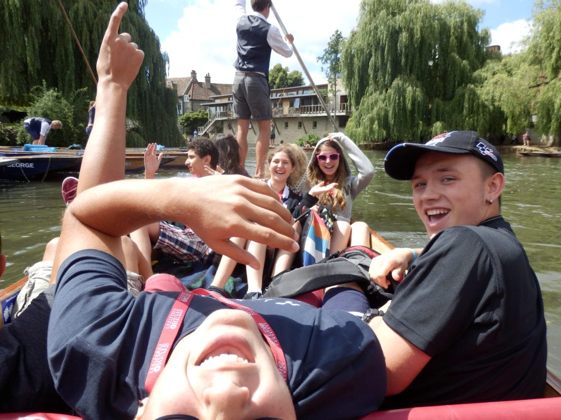 Group of Sir William English summer camp students smiling and laughing in a punt on the River Cam