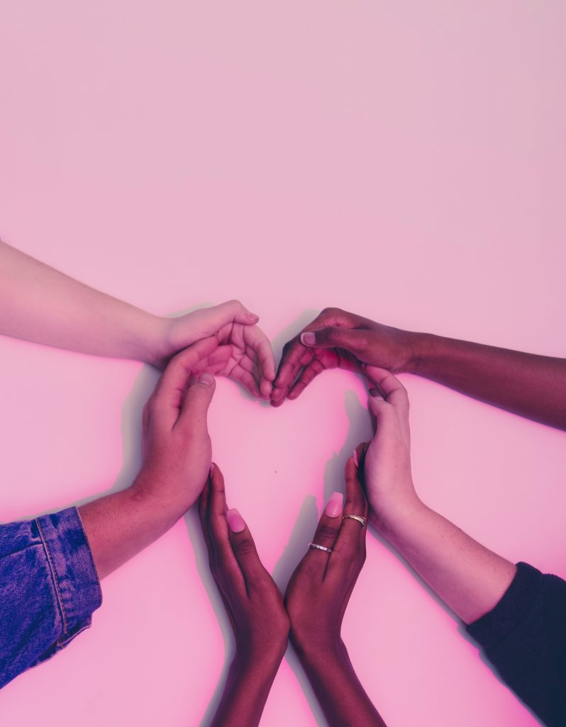 Six hands of people with a variety of different skin tones coming together in the shape of a heart on a dusty pink background.