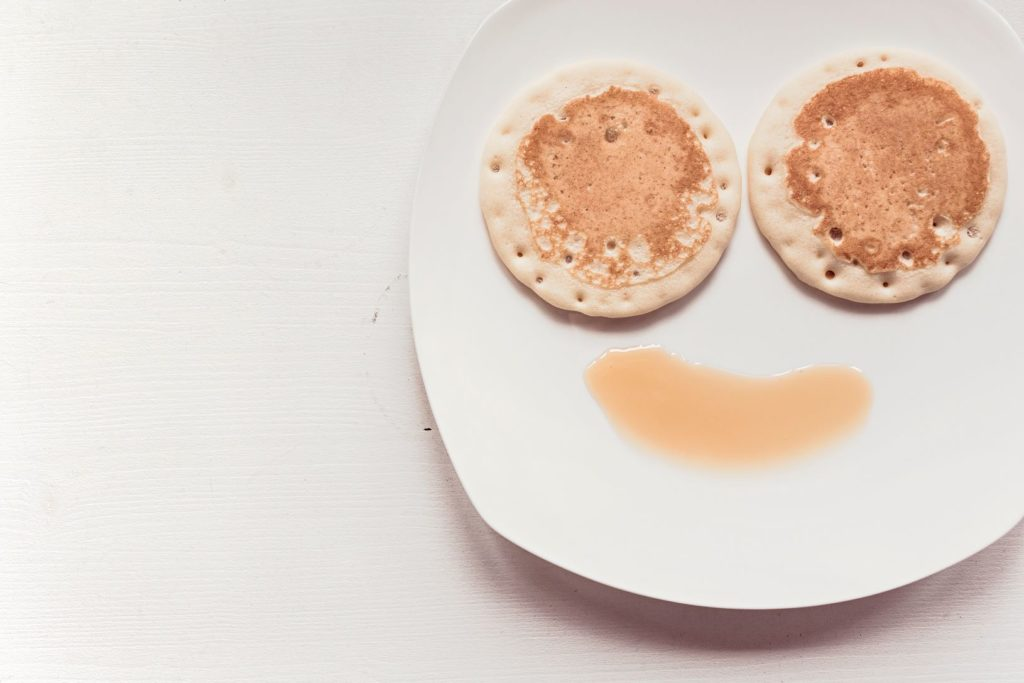 Two pancakes on a white plate with a splash of syrup underneath, arranged to look like a smiley face.